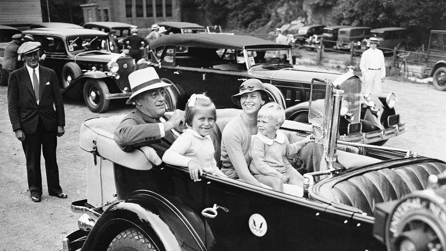 FILE - In this Aug. 20, 1933 file photo, U.S. President Franklin D. Roosevelt sits in his car with his daughter Anna Eleanor Dall and her two children, Anna Eleanor Roosevelt, and Curtis Roosevelt, as he arrived back his home in Hyde Park, N.Y., to resume his vacation following an eventful week in Washington dealing with the National Recovery Administration. Curtis Roosevelt, who lived in the White House as a child when his grandfather was president and worked for two decades at the U.N., has died at 86 on Wednesday, Sept. 26, 2016. (AP Photo)