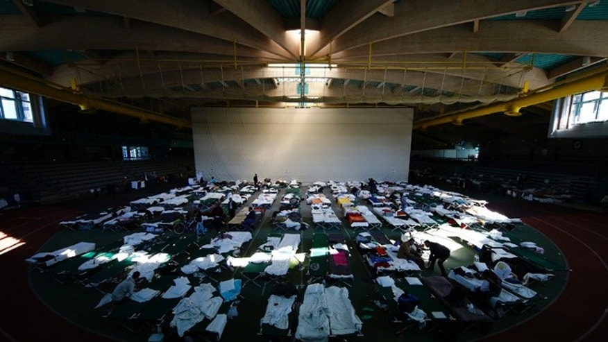 Refugees rest at a temporary shelter in a sports hall in Hanau, Germany.