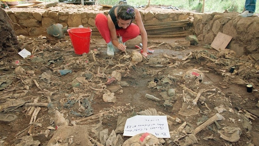 FILE - In this Oct. 23, 1992 file photo, forensic anthropologist Claudia Bernard, from Argentina, brushes dirt from human remains, in El Mozote, El Salvador. A human rights advocate said Saturday, Oct. 1, 2016 that Judge Jorge Guzman Urquilla has granted  reopening a probe into the El Mozote massacre. A postwar truth commission concluded that the army massacred at least 500 people in El Mozote and surrounding villages in three days in December 1981. Victims' rights advocates put the number closer to 1,000. (AP Photo/Michael Stravato, File)