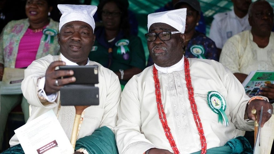 Nigerian white cap chiefs take a selfie during the 56th anniversary celebrations of Nigerian independence, in Lagos, Nigeria, Saturday, Oct. 1, 2016. (AP Photo/Sunday Alamba)