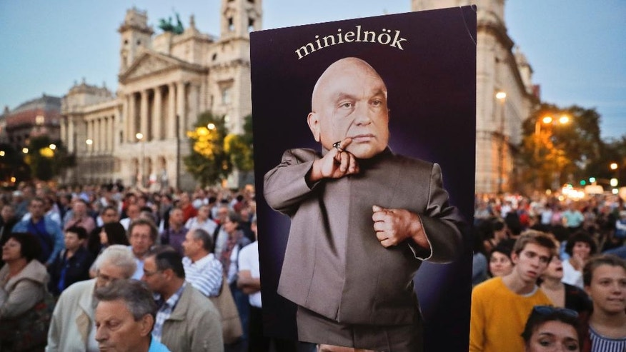"A man holds a banner depicting Hungarian Premier Viktor Orban, the reads ""mini-prime minister"" during a protest against Orban's policies regarding migrants in Budapest, Hungary, Friday, Sept. 30, 2016.  Hungarians will vote Sunday in a referendum which Prime Minister Viktor Orban hopes will give his government the popular support it seeks to oppose any future plans by the European Union to resettle asylum seekers among its member states.(AP Photo/Vadim Ghirda)"