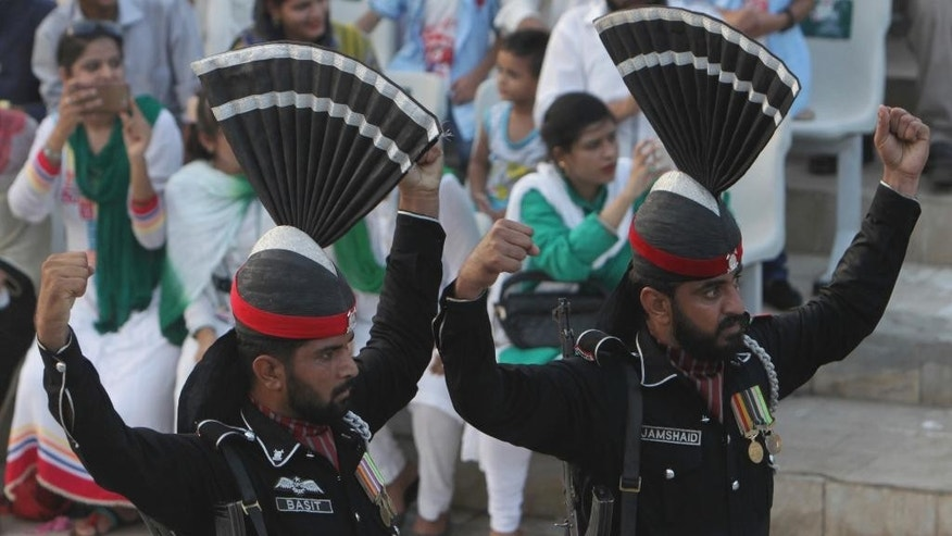 Pakistani border guards gesture while looking at their Indian counterpart during a daily border closing ceremony at sunset, at the Wagha border post, Pakistan, Saturday, Oct 1, 2016. A routine daily flag-lowering ceremony at an Indian-Pakistani border crossing has become a show of strength and patriotism on the Pakistani side thanks to simmering tensions between the two nuclear-armed neighbors. (AP Photo/K.M. Chaudhry)