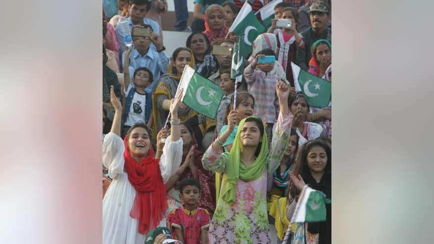 Pakistani spectators wave their national flags during a daily border closing ceremony at the Wagha border post in Pakistan, Saturday, Oct 1, 2016. A routine daily flag-lowering ceremony at an Indian-Pakistani border crossing has become a show of strength and patriotism on the Pakistani side thanks to simmering tensions between the two nuclear-armed neighbors. (AP Photo/K.M. Chaudhry)