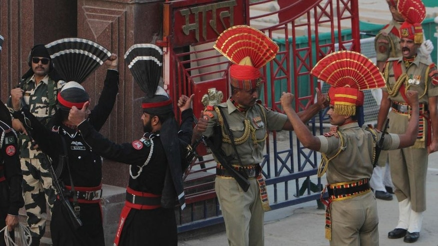 Pakistani border guards in black uniform take part in a daily border closing ceremony with their Indian counterpart at the Wagha border post in Pakistan, Saturday, Oct 1, 2016. A routine daily flag-lowering ceremony at an Indian-Pakistani border crossing has become a show of strength and patriotism on the Pakistani side thanks to simmering tensions between the two nuclear-armed neighbors. (AP Photo/K.M. Chaudhry)