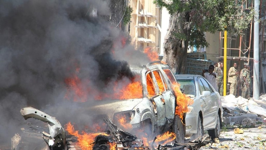 A burning car, after an explosion, in Mogadishu Somalia, Saturday, Oct. 1, 2016. A Somali police officer says a car bomb struck the entrance of a restaurant in the Somali capital Saturday, killing two people. Capt. Mohamed Hussein said that the blast occurred as Blue Sky restaurant which is close to the presidential palace was packed with diners. (AP Photo/Farah Abdi Warsameh)
