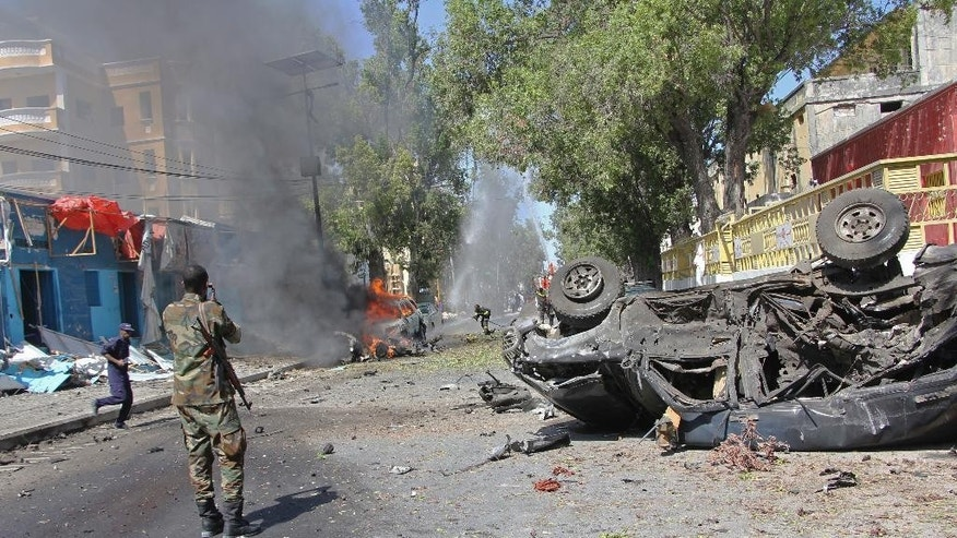 AS Somali soldier stands  near to the burning  wreckage of a car, after an explosion, in Mogadishu Somalia, Saturday, Oct. 1, 2016. A Somali police officer says a car bomb struck the entrance of a restaurant in the Somali capital Saturday, killing two people. Capt. Mohamed Hussein said that the blast occurred as Blue Sky restaurant which is close to the presidential palace was packed with diners. (AP Photo/Farah Abdi Warsameh)