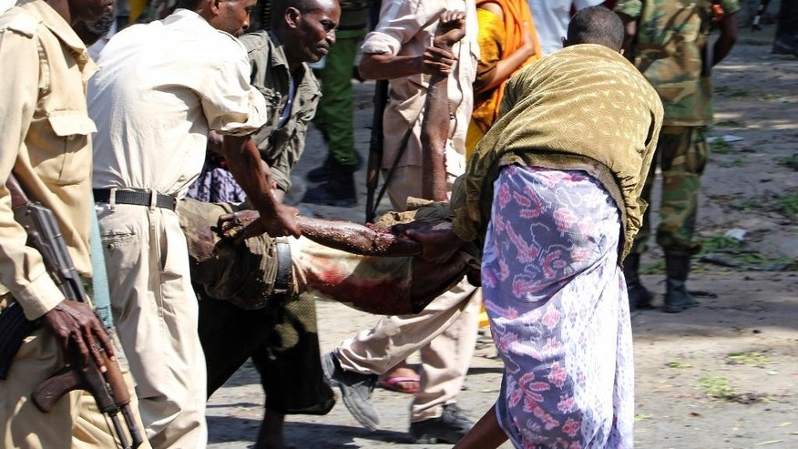 Somali men carry the body of a victim after an explosion outside a restaurant, in Mogadishu Somalia, Saturday, Oct. 1, 2016. A Somali police officer says a car bomb struck the entrance of a restaurant in the Somali capital Saturday, killing two people. Capt. Mohamed Hussein said that the blast occurred as Blue Sky restaurant which is close to the presidential palace was packed with diners. (AP Photo/Farah Abdi Warsameh)
