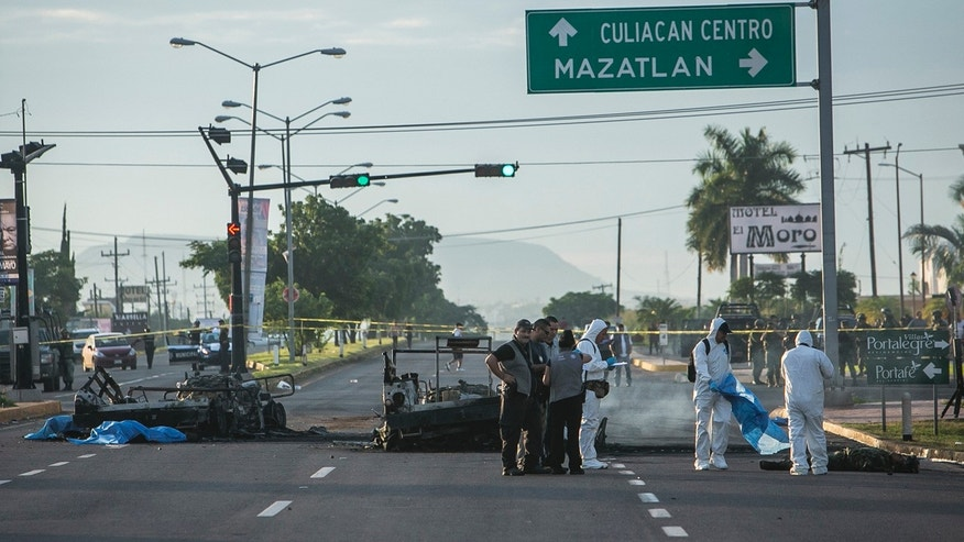 Sept. 30, 2016: Police investigators examine the site where a military convoy was ambushed using grenades and high-powered guns, killing five soldiers in the city of Culiacan, Mexico.