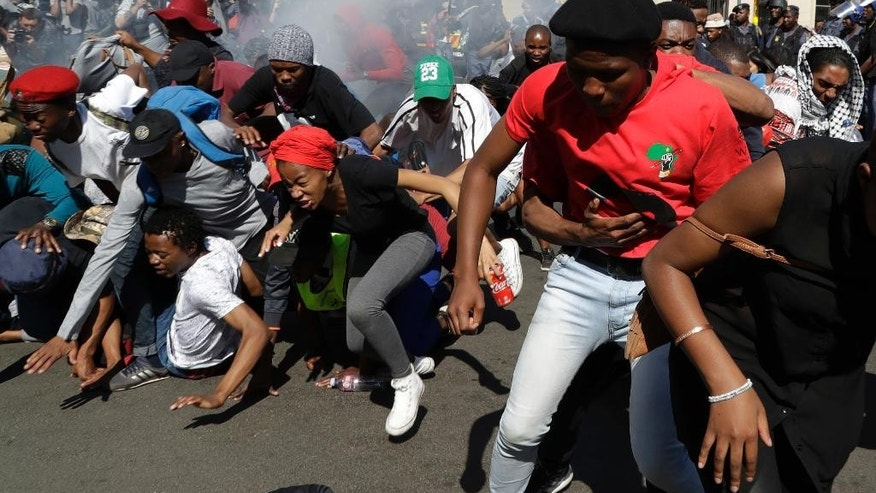 FILE - In this file photo dated Wednesday, Sept. 21, 2016, students run for cover after police fired stun grenades and rubber bullets in an attempt to disperse them during a protest, in Johannesburg, South Africa.  Grievances over economic inequities are fueling unrest that has forced the closure of some of South Africa's most prominent universities, with the government alleging a radical minority has brought campuses to a standstill over financing of higher education. (AP Photo/Themba Hadebe, FILE)