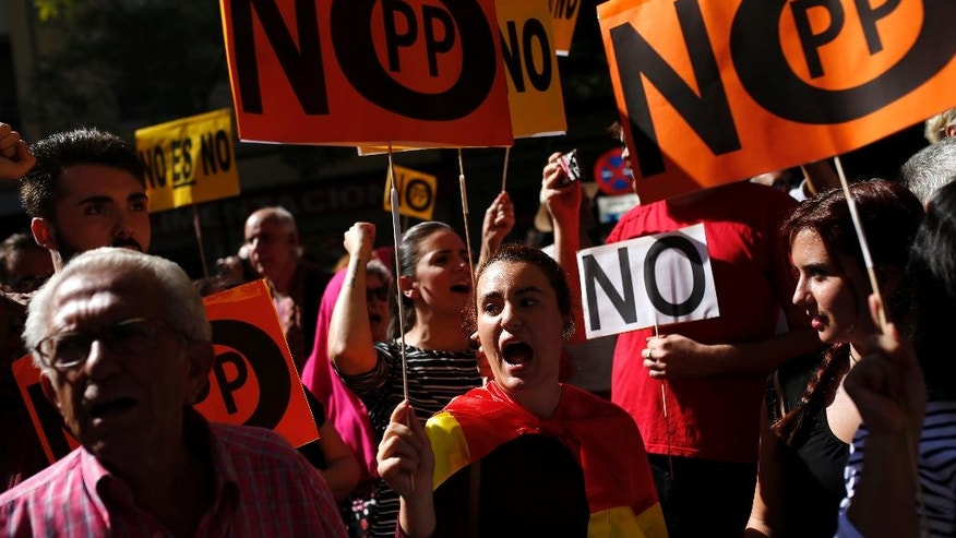 """Supporters of Spain's Socialist party leader Pedro Sanchez hold placards that read: """"No Popular Party"""" as they shout slogans outside the party headquarters in Madrid, Saturday, Oct. 1, 2016. Spain's Socialist party is facing strong internal discord as they vote to decide if they will keep or oust their leader Pedro Sanchez, who has been leading opposition to acting conservative Prime Minister Mariano Rajoy's efforts to build a minority government and end a nine-month political deadlock. (AP Photo/Francisco Seco)"""
