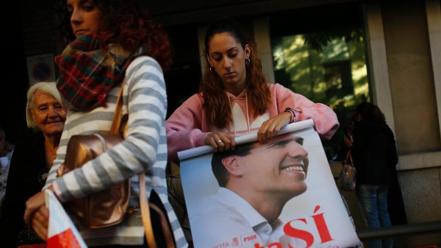 A woman rolls up a poster with the photograph of Spain's Socialist party leader Pedro Sanchez outside the party headquarters in Madrid, Saturday, Oct. 1, 2016. Spain's Socialist party is facing strong internal discord as they vote to decide if they will keep or oust their leader Pedro Sanchez, who has been leading opposition to acting conservative Prime Minister Mariano Rajoy's efforts to build a minority government and end a nine-month political deadlock. (AP Photo/Francisco Seco)