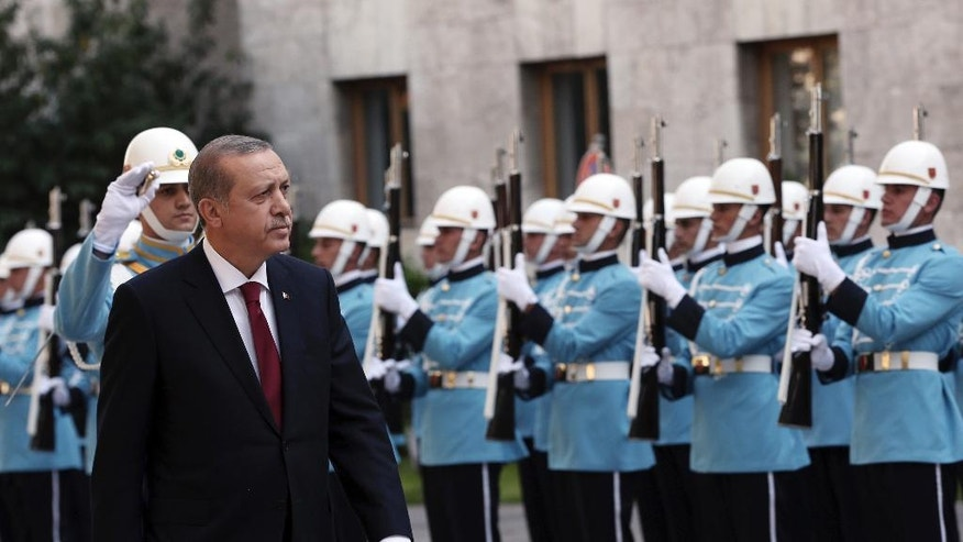 Turkey's President Recep Tayyip Erdogan inspects a military honour guard as he arrives to address the parliament in Ankara, Turkey, Saturday, Oct. 1, 2016. Erdogan hinted on Thursday that the three-month state of emergency declared following the failed July 15 coup could be extended to over a year. (AP Photo/Burhan Ozbilici)