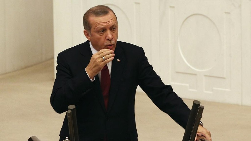 Turkey's President Recep Tayyip Erdogan addresses the parliament in Ankara, Turkey, Saturday, Oct. 1, 2016. Erdogan hinted on Thursday that the three-month state of emergency declared following the failed July 15 coup could be extended to over a year. (AP Photo/Burhan Ozbilici)
