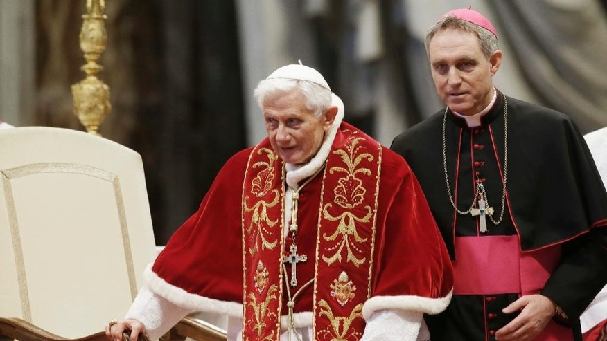 FILE  - This Feb. 9, 2013 file photo shows Pope Benedict XVI flanked by personal secretary Archbishop Georg Gaenswein during a Mass to mark the 900th anniversary of the Order of the Knights of Malta in St. Peter's Basilica at the Vatican. Monsignor Georg Gaenswein, Benedict's personal aide, in comments published Sunday, Oct. 2, 2016, in Corriere della Sera, said a doctor told Benedict to stop taking trans-Atlantic flights.  (AP Photo/Gregorio Borgia, files)