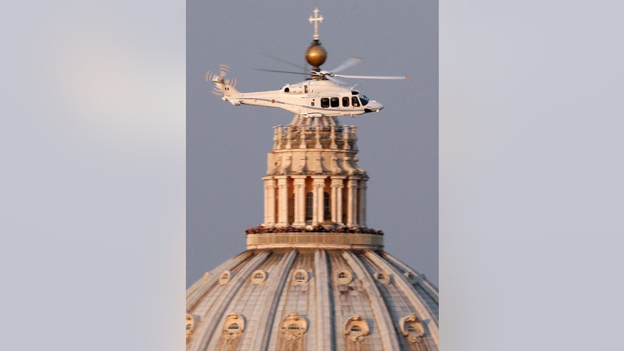 FILE - This Feb. 28, 2013 file photo shows a helicopter carrying Pope Benedict XVI flying over St. Peter's Basilica as it leaves the Vatican for Castel Gandolfo. Monsignor Georg Gaenswein, Benedict's personal aide, in comments published Sunday, Oct. 2, 2016, in Corriere della Sera, said a doctor told Benedict to stop taking trans-Atlantic flights.  (AP Photo/Michael Sohn, files)