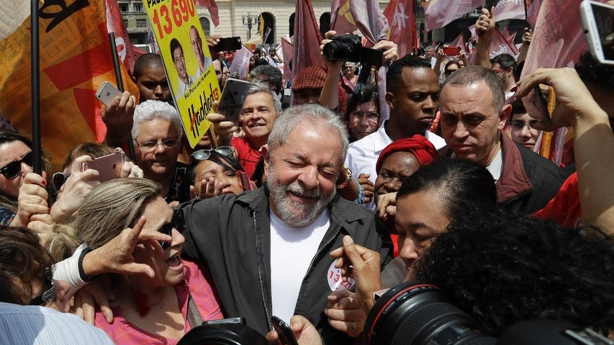 Brazil's former President Luiz Inacio Lula da Silva is surrounded by supporters as he campaigns for Sao Paulo's Mayor Fernando Haddad, who's running for re-election with the Workers Party in Sao Paulo, Brazil, Friday, Sept. 30, 2016. The first round of nationwide mayoral elections are scheduled for Sunday, Oct. 2. (AP Photo/Andre Penner)
