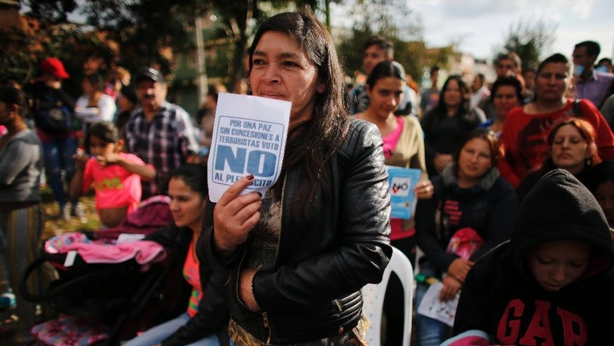 """A woman attends an event to promote the """"No"""" vote in the upcoming referendum on the peace deal signed between the Colombian government and rebels of the Revolutionary Armed Forces of Colombia, FARC, in Bogota, Colombia, Saturday, Oct 1, 2016. Colombians go to the polls Sunday in a referendum where they will be asked to ratify or reject the accord. (AP Photo/Ariana Cubillos)"""