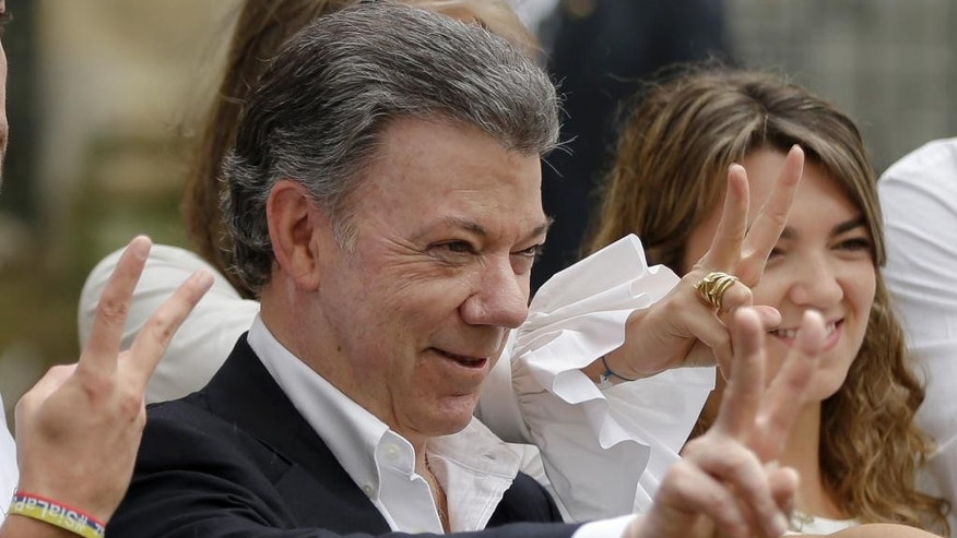 Colombia's President Juan Manuel Santos makes the victory sign after voting in a referendum to decide whether or not to support the peace deal he signed with rebels of the Revolutionary Armed Forces of Colombia, FARC, in Bogota, Colombia, Sunday, Oct. 2, 2016.   (AP Photo/Ricardo Mazalan)