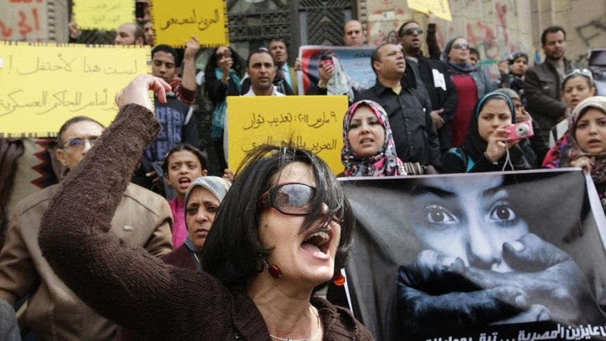 "FILE - In this Friday, March 16, 2012, file photo, an Egyptian activist shouts anti-military Supreme Council slogans during a demonstration in front of Cairo's high court, Egypt. An independent Egyptian daily says the state's top women's advocacy group has filed a complaint with the chief prosecutor against a lawmaker who called for mandatory virginity tests for women seeking university admission. Arabic reads "" March 9, 2011, protesters torture "" and "" We did not want the Egyptian woman to be a second-class citizen"". (AP Photo/Amr Nabil)"