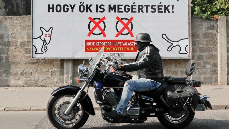 "A man rides a motorcycle by a poster that reads in Hungarian ""Let's send a message to Budapest, so they also understand! A stupid answer to a stupid question! Cast an invalid vote!"" in opposition to Hungarian Premier Minister's Viktor Orban policies on migrants in Budapest, Hungary, Saturday, Oct. 1, 2016. Hungarians will vote Sunday in a referendum which Prime Minister Viktor Orban hopes will give his government the popular support it seeks to oppose any future plans by the European Union to resettle asylum seekers among its member states. (AP Photo/Vadim Ghirda)"
