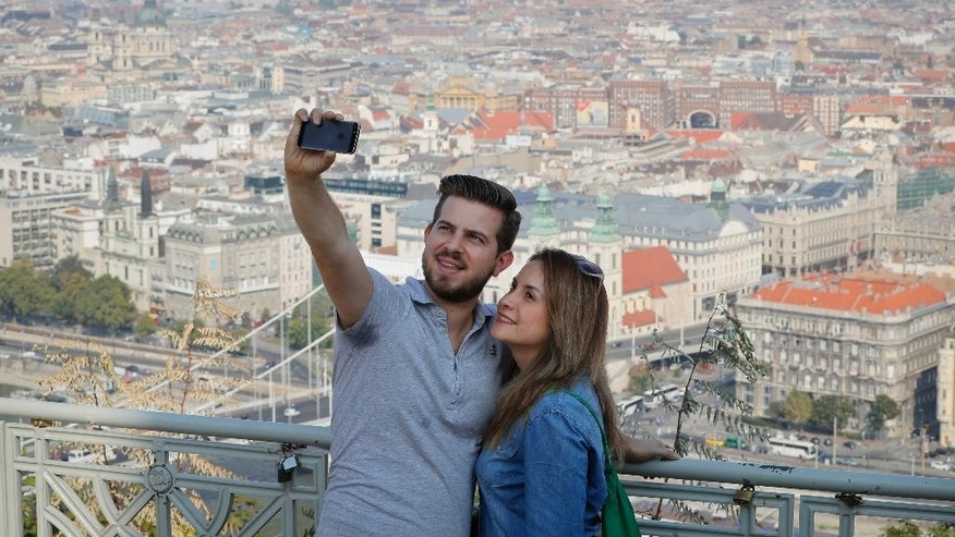 A couple takes a selfie from a hill overlooking the Hungarian capital in Budapest, Hungary, Saturday, Oct. 1, 2016. Hungarians will vote Sunday in a referendum which Prime Minister Viktor Orban hopes will give his government the popular support it seeks to oppose any future plans by the European Union to resettle asylum seekers among its member states. (AP Photo/Vadim Ghirda)