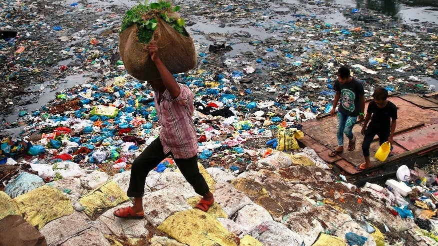 A man carries a sack of vegetables as he walks past a polluted canal littered with plastic bags and other garbage in Mumbai, India, Sunday, Oct. 2, 2016. India is scheduled to deposit the ratification instruments of the Paris Agreement on Climate Change with the United Nations on Sunday, the anniversary of Mahatma Gandhi's birth, who believed in a minimum carbon footprint. India accounts for about 4.5 percent of emissions. (AP Photo/Rafiq Maqbool)