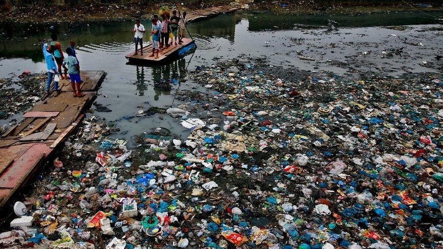 A man guides a raft through a polluted canal littered with plastic bags and other garbage in Mumbai, India, Sunday, Oct. 2, 2016. India is scheduled to deposit the ratification instruments of the Paris Agreement on Climate Change with the U.N. on Oct. 2, the anniversary of Mahatma Gandhi's birth, who believed in a minimum carbon footprint. India accounts for about 4.5 percent of emissions. (AP Photo/Rafiq Maqbool)