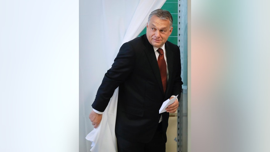 Hungarian Prime Minister Viktor Orban exits a voting cabin after voting in the referendum in Budapest, Hungary, Sunday, Oct. 2, 2016. Hungarians vote in a referendum which Orban hopes will give his government the popular support it seeks to oppose any future plans by the European Union to resettle asylum seekers among its member states. (AP Photo/Vadim Ghirda)