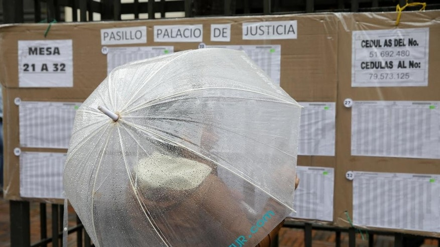 A voter looks for her polling station during a referendum to decide whether or not to support a peace deal signed between the Colombian government and rebels of the Revolutionary Armed Forces of Colombia, FARC, in Bogota, Colombia, Sunday, Oct. 2, 2016. The deal will end more than 5 decades of conflict between the FARC and the government.  (AP Photo/Ricardo Mazalan)