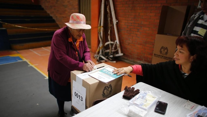 A woman votes during a referendum to decide whether or not to support a peace deal signed between the Colombian government and rebels of the Revolutionary Armed Forces of Colombia, FARC, in Guasca, Colombia, Sunday, Oct. 2, 2016. The deal will end more than 5 decades of conflict between the FARC and the government. (AP Photo/Ariana Cubillos)
