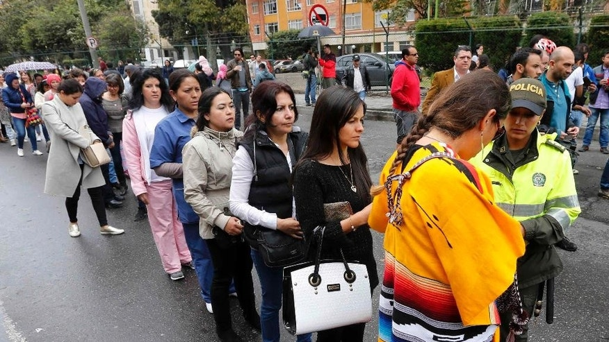 Women line up outside a polling station during a referendum to decide whether or not to support a peace deal signed between the Colombian government and rebels of the Revolutionary Armed Forces of Colombia, FARC, in Bogota, Colombia, Sunday, Oct. 2, 2016. The deal will end more than 5 decades of conflict between the FARC and the government. (AP Photo/Fernando Vergara)