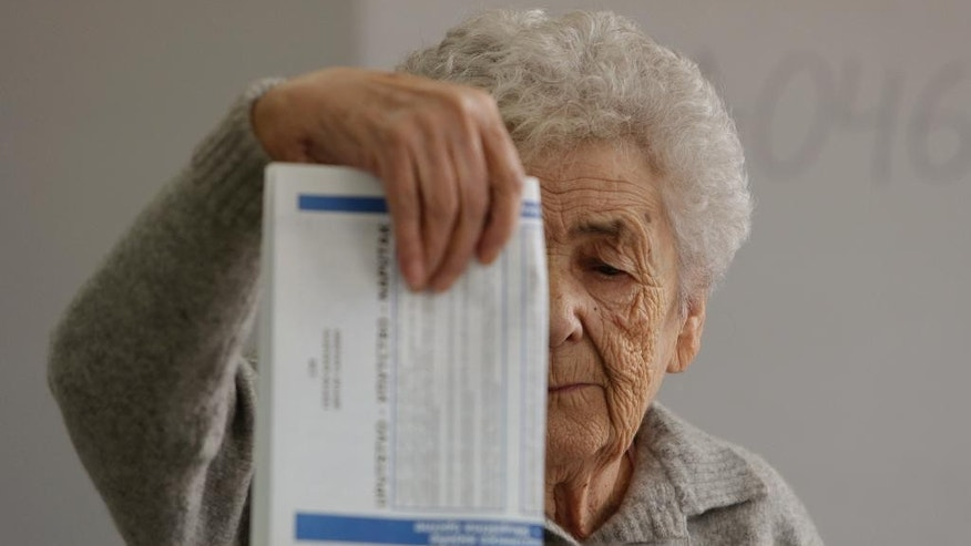 A Bosnian woman casts her ballot at a poling station in the Bosnian capital of Sarajevo Sunday, Oct. 2, 2016. Bosnians are voting on Sunday in municipal elections marked by a battle in the Bosnian Serb half of the country between a pro-European Union coalition and the pro-Russia separatist party that has ruled that region for more than a decade. (AP Photo/Amel Emric)