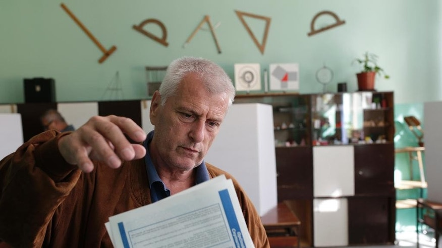 A Bosnian man casts his ballot at a poling station in the Bosnian capital of Sarajevo Sunday, Oct. 2, 2016. Bosnians are voting on Sunday in municipal elections marked by a battle in the Bosnian Serb half of the country between a pro-European Union coalition and the pro-Russia separatist party that has ruled that region for more than a decade. (AP Photo/Amel Emric)