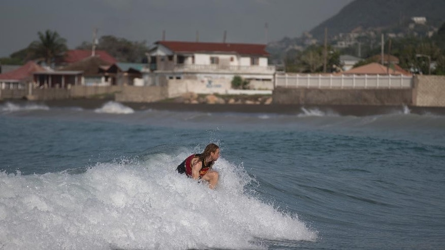 A man surfs at Wickie Wackie Beach before the arrival of Hurricane Matthew in Kingston, Jamaica, Sunday, Oct. 2, 2016. A powerful Hurricane Matthew moved slowly across the Caribbean Sea Sunday with winds of 140 mph (220 kph). A hurricane warning is in effect for Jamaica, Cuba and Haiti. (AP Photo/Eduardo Verdugo)