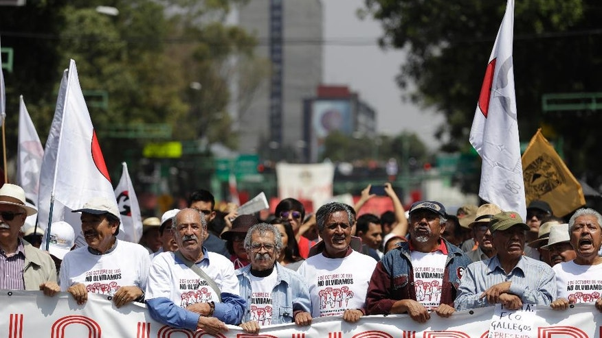 Protestors walk behind a banner decrying impunity, during a march commemorating the anniversary of the Tlatelolco Massacre, in Mexico City, Sunday, Oct. 2, 2016. Every year Mexico marks the anniversary of the 1968 massacre where students and civilians were killed by the military and police.(AP Photo/Rebecca Blackwell)