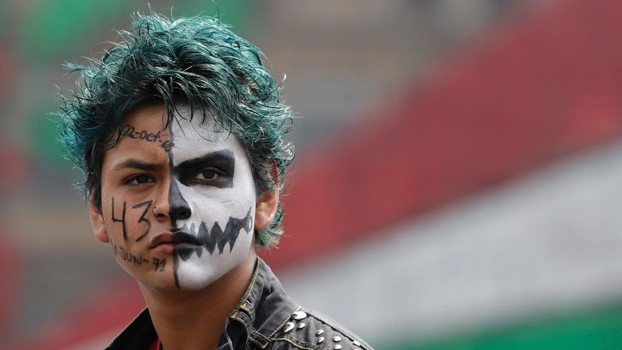 A protestor with a painted face participates in a march commemorating the anniversary of the Tlatelolco Massacre, in Mexico City, Sunday, Oct. 2, 2016. Every year Mexico marks the anniversary of the 1968 massacre where students and civilians were killed by the military and police.(AP Photo/Rebecca Blackwell)