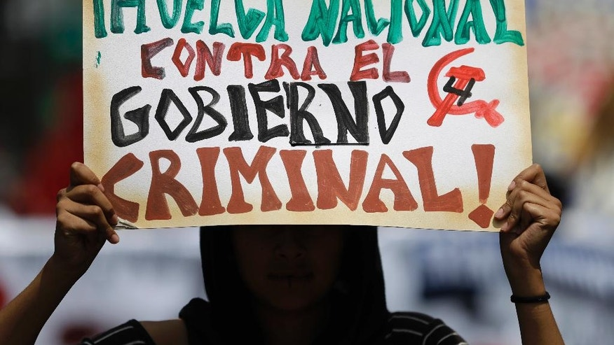 """A member of a workers group holds up a sign calling for a """"National strike against the criminal government,"""" during a march commemorating the anniversary of the Tlatelolco Massacre, in Mexico City, Sunday, Oct. 2, 2016. Every year Mexico marks the anniversary of the 1968 massacre where students and civilians were killed by the military and police.(AP Photo/Rebecca Blackwell)"""