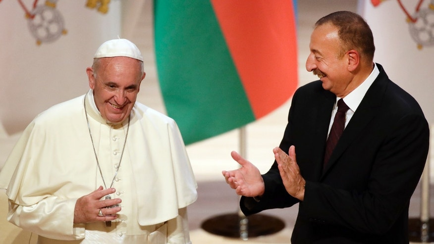 Azerbaijan's President Ilham Aliyev applauds Pope Francis during their meeting Sunday.