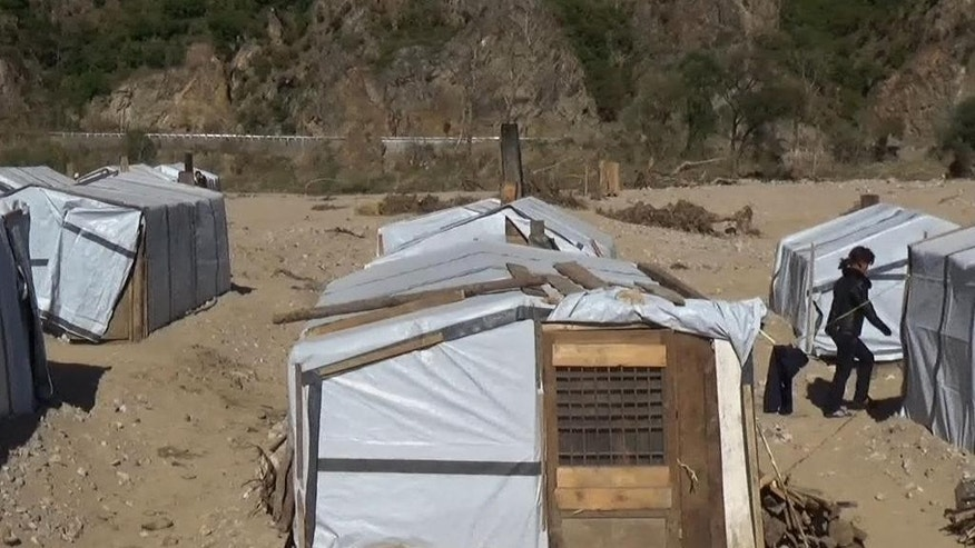 In this image made from TV made available Sunday Oct. 2, 2016, temporary shelters set up for victims amid rubble and mud-caked areas of destruction left in the wake of massive flooding in Hoeryong City, North Korea, Wednesday Sept. 28, 2016.  One month after devastating floods hit this remote area of North Korea, the Red Cross is calling for urgent help for the thousands of people desperate to rebuild their lives before harsh winter conditions set in. (Red Cross via AP)