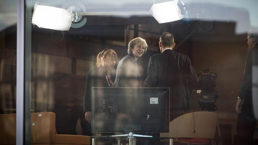 Britain's Prime Minister Theresa May, 2nd left, arrives ahead of a TV interview with journalist presenter Andrew Marr, 3rd left, at BBC studios in Birmingham, England, before the start of the annual Conservative party conference, Sunday Oct. 2, 2016.  During the interview May said Britain will trigger the Article 50 formal process for leaving the European Union, Brexit, before the end of March 2017, setting the nation on a course to leave the 28-nation European trading bloc by 2019. (Stefan Rousseau / PA via AP)
