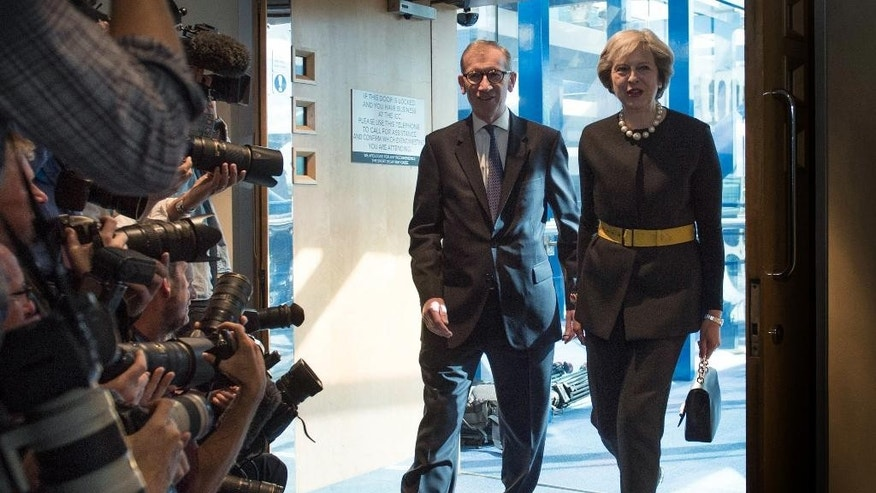 Britain's Prime Minister Theresa May and her husband Philip are watched by the media as they arrive at the Conservative Party Conference in Birmingham, England, Sunday Oct. 2, 2016.  During a BBC TV interview earlier Sunday, May said Britain will trigger the Article 50 formal process for leaving the European Union trading bloc, Brexit, before the end of March 2017, which she said would feature in her speech to the party conference. (Stefan Rousseau / PA via AP)
