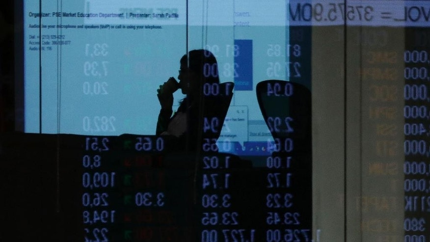 In this Friday, Sept. 30, 2016 photo, an electronic board of the Philippine Stock Exchange is reflected on the mirror as a woman sips her drink at the financial district of Makati, south of Manila, Philippines. Analysts and businessmen point to uncertainties about Philippine President Rodrigo Duterte's policies and flip-flopping pronouncements as largely to blame for foreign selling in the stock market and the peso's plunge to a seven-year low, reversing initial optimism after his June 30 inauguration. (AP Photo/Aaron Favila)