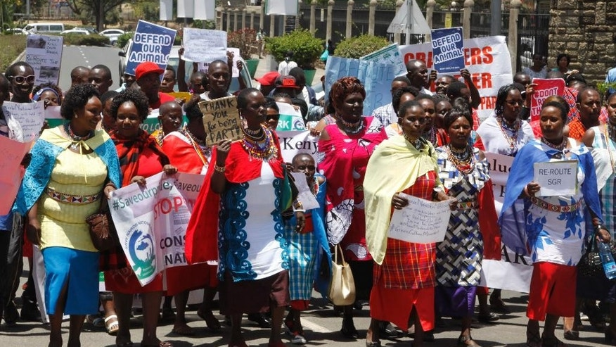 Kenyans hold up signs as they attend a protest to protect the Nairobi National Park in Nairobi Kenya Monday, Oct.  3, 2016. About 100 protesters have petitioned the office of Kenya's president urging him to intervene and stop the planned construction of an elevated railway line through Nairobi National Park. (AP Photo/Khalil Senosi)