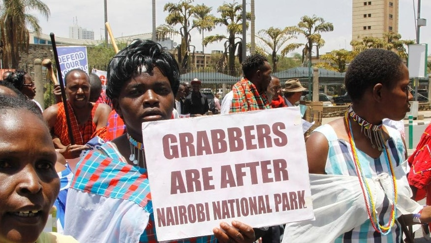 Kenyans hold up signs as they attend a protest to protect the Nairobi National Park in Nairobi Kenya Monday, Oct.  3, 2016.About 100 protesters have petitioned the office of Kenya's president urging him to intervene and stop the planned construction of an elevated railway line through Nairobi National Park.  (AP Photo/Khalil Senosi)