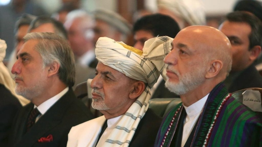 File, in this Thursday, Sept. 29, 2016, photo, Afghan President Ashraf Ghani, center, former President Hamid Karzai, right, and Chief Executive Abdullah Abdullah, left, watch the live broadcast of Gulbuddin Hekmatyar at the presidential palace in Kabul, Afghanistan. Afghanistan's leaders will head to Brussels this week, seeking billions of dollars in aid as the country confronts an increasingly powerful Taliban insurgency and pervasive corruption. Ghani and Abdullah hope to secure pledges totaling about $3 billion a year at the conference, which will be held on Tuesday, Oct. 4, and Wednesday, Oct. 5. (AP Photo/Rahmat Gul, File)