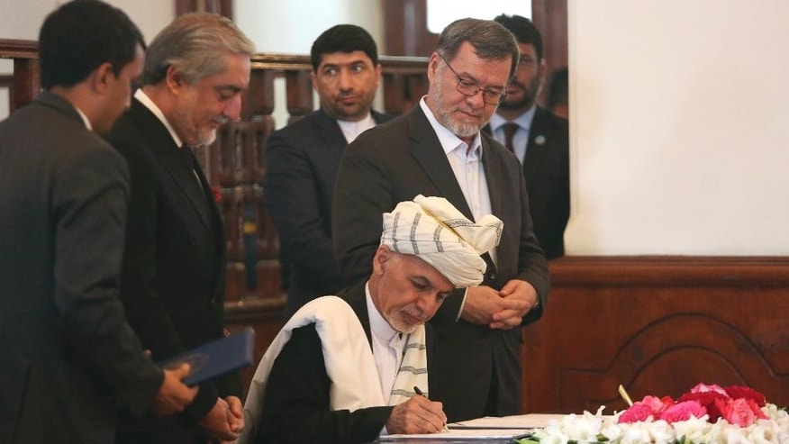 FILE - In this Thursday, Sept. 29, 2016, file photo, Afghan President Ashraf Ghani, center, signs a peace agreement as Chief Executive Abdullah Abdullah, second left, watches at the presidential palace in Kabul, Afghanistan. Afghanistan's leaders will head to Brussels this week, seeking billions of dollars in aid as the country confronts an increasingly powerful Taliban insurgency and pervasive corruption. Ghani and Abdullah hope to secure pledges totaling about $3 billion a year at the conference, which will be held on Tuesday, Oct. 4 and Wednesday, Oct. 5. (AP Photo/Rahmat Gul, File)