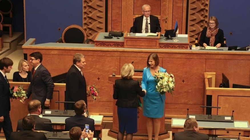 Kersti Kaljulaid, center, is congratulated on being elected a new president in the Estonian parliament in Tallinn, Estonia, Monday, Oct. 3, 2016. Estonia finally has chosen a new president, who will be the Baltic country's first female leader. After two failed votes and weeks of heated debate, lawmakers on Monday unanimously elected European Union accountant Kersti Kaljulaid. (AP Photo/Vitnija Saldava)