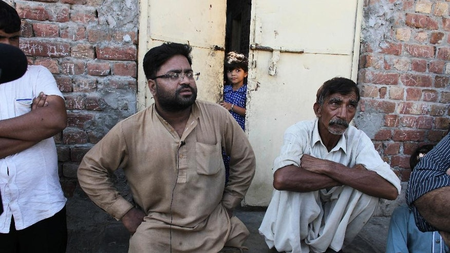 "In this photo taken on Thursday, Sept. 1, 2016, neighbors of Mubeen Rajhu, who killed his sister Tasleem, talk about the murder in Lahore, Pakistan. Rajhu who couldn't stand the teasing, accusations and whispers from co-workers and neighbors that his sister was having an affair and with a Christian. The taunts were relentless. ""What kind of a man are you?"" his workmates at the coal-fired steel mill where he had worked for nearly four years asked. His neighbors sneered as he passed. ""Do you have no honor?"" they asked. (AP Photo/K.M. Chaudary)"
