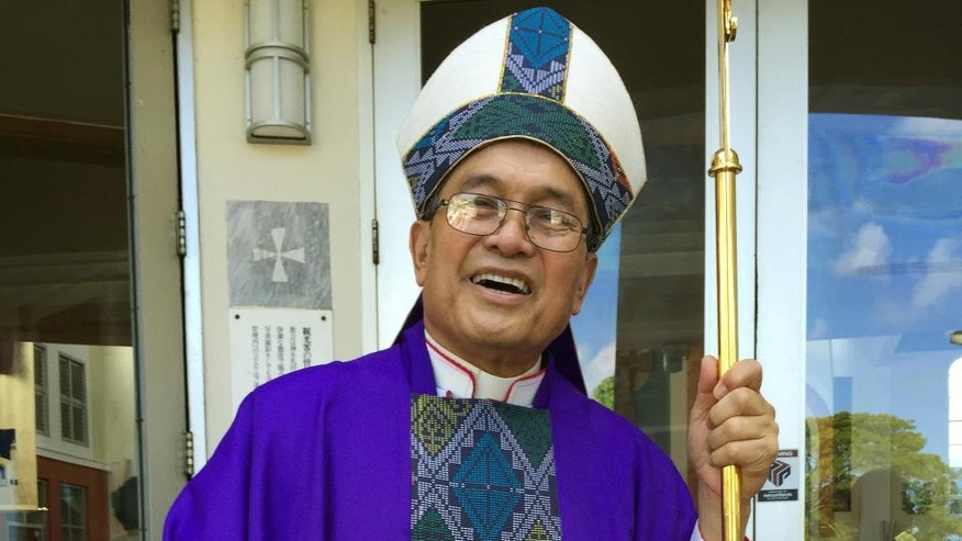 FILE - In this November 2014 file photo, Archbishop Anthony Apuron stands in front of the Dulce Nombre de Maria Cathedral Basilica in Hagatna, Guam. The U.S. territory of Guam, where almost everyone is Catholic, has been ripped apart by claims the archbishop abused altar boys. Apuron has denied allegations he molested multiple altar boys. (AP Photo/Grace Garces Bordallo, File)