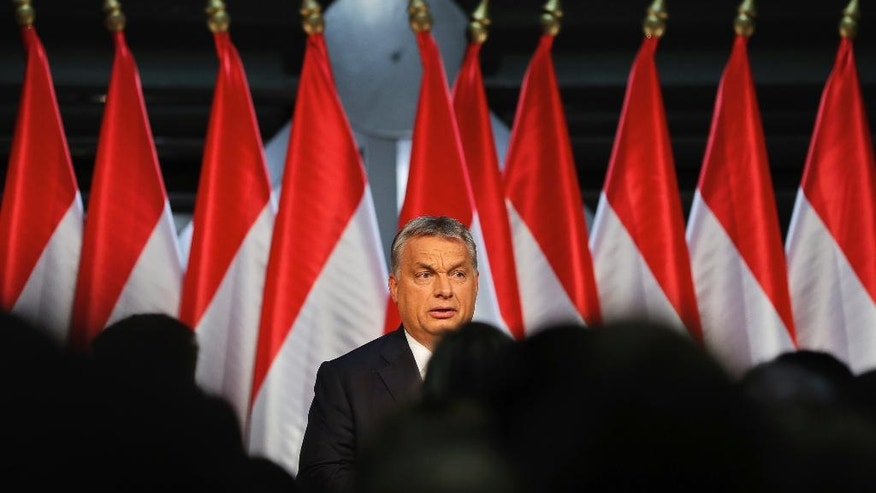 Hungarian Premier Viktor Orban looks at supporters before delivering a speech in  Budapest, Hungary, Sunday, Oct. 2, 2016. Hungarians overwhelmingly supported the government in a referendum on Sunday called to oppose any future, mandatory European Union quotas for accepting relocated asylum seekers but nearly complete official results showed the ballot was invalid due to low voter turnout. (AP Photo/Vadim Ghirda)